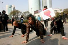 3 men crawling on the ground in chain leashes led by a woman, claim to be promoting respect for women