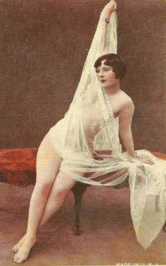 ARCADE CARD – UNKNOWN PUBLISHER – WOMAN SITTING ON STOOL WITH ONE ARM UP HOLDING LENGTH OF LACE COVERING HER – TINTED – 1920s