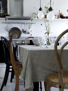 hanging bulbs, mismatched chairs, industrial counter, frayed table cloth, what's not to love