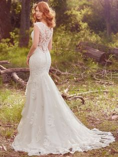 Maggie Sottero - ZALIA, A three-tiered skirt hemmed in scalloped lace appliqués adds romance and whimsy to this classic fit-and-flare wedding dress. Lace motifs adorn the bodice, illusion V-neckline, illusion straps, and illusion open-back. Finished with covered buttons over zipper closure.
