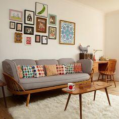 O colorido das almofadas e dos quadros quebra o cinza com madeira dos móveis :: lindo!
