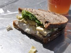 Black olive bread is spread with a touch of pesto, then stocked with soft ricotta cheese, topped with marinated artichoke hearts, and sprinkled with a bit of arugula for that slight crunch and bitterness.