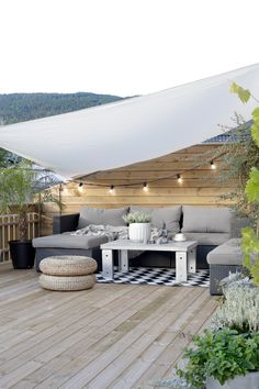 deck. white sail. gray outdoor sofa. cane ottomans.