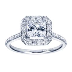 This sparkling diamond engagement ring in a prong setting is paired with a princess cut diamond surrounded by a border of diamonds to enhance its radiance. Make it a truly special day for your beloved when she wears this 14K White Gold Princess Diamond Side-Stones Contemporary Halo Engagement Ring.