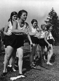 """Reinwarzhofen. Zeltlager des Bundes Deutscher Mädel (BdM) auf dem Zeltlagerplatz """"Göring-Espan"""". Mädchengruppe in Sportbekleidung als Zuschauerinnen"""