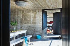 Patio interno con paredes y techo de hormigón expuesto con grandes puertas anchas.