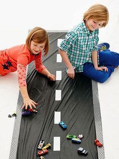 Fold a 54- by 108-inch black vinyl tablecloth in half lengthwise to create a strip 27 inches wide. Line the edges with checkerboard duct tape and add white duct tape lane markings. Adhere the cloth to the floor with a low-tack tape,  such as painter's tape, then let kids race -- or, more likely, crash! -- their cars.