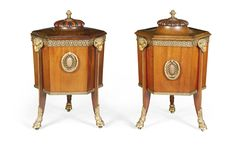 A matched pair of gilt-bronze-mounted mahogany wine coolers George III style, late 19th century each of hexagonal form, with pine cone finials on half lobed lids, one hinged the other removable and revealing an interior lined with lead and divisions for bottles the other without a liner, the wasted sides with alternating handles and legs surmounted by rams head masks, beading and ending in hoof feet with concealed castors