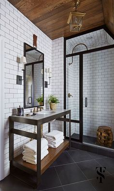 Subway tile, black steel shower door, dark mirror frame and sink cabinet and slate floors