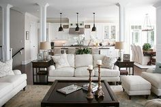 White walls, white kitchen cabinets, light living room with dark furniture, dark wood floors.