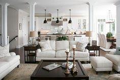 White walls, white kitchen cabinets, light living room with dark furniture, dark…
