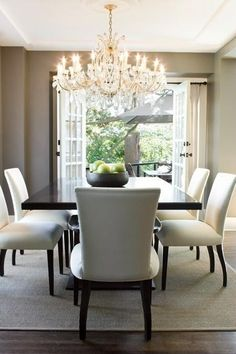 Beautiful Black and White Dining Room with Crystal Chandelier, White Upholstered Chairs, Grey Walls, French Doors, White Drapery with Black Rod