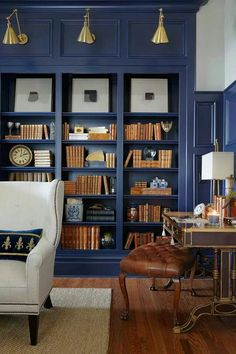 Dark gray built in shelves with contrasting leather bound books and art display.