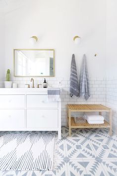 modern white bathroom renovation complete with patterned cement tile Photography…