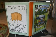 """huge book statue created by lauren haldeman, celebrating reading & writing in iowa city, unesco city of literature, """"celebrate literature, discover your story"""" in coralville, iowa"""