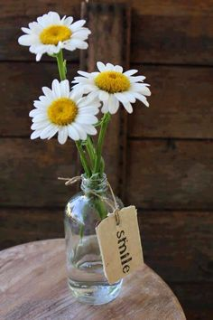 White flowers in vase with smile tag