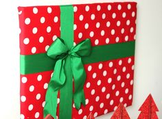 diy Christmas wall decor: Wrap your pictures on the wall and adorn w/ ribbon to create a festive Christmas Display! Use dollar store wrapping paper - cheep!