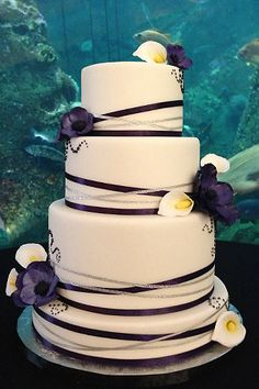 White varying tier wedding cake with pleated tiers hand sculpted white wedding cake with hand sculpted purple anemone and white calla lillie sugar flowers purple mightylinksfo