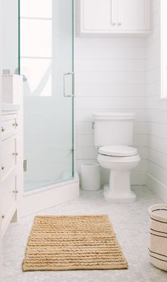 Beneath white shaker cabinets adorned with polished nickel knobs and mounted against a shiplap trim, a white porcelain toilet is fixed beside a corner walk-in shower finished with a seamless glass enclosure. Shiplap Trim, Garage Guest House, White Shaker Cabinets, Over Toilet, Glazed Brick, Living Room White, White Houses, Interiores Design, Decoration