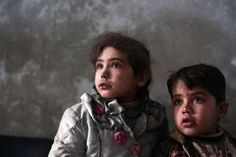 Syrian children wait for treatment at a makeshift clinic in the besieged rebel town of Douma