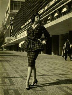 Década de 60 - Conjunto Nacional na avenida Paulista com rua Augusta. Entrada para o Cine Astor (ao fundo), a manequim bem vestidinha em primeiro plano e à direita caminha um mendigo...
