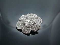 Spilla camelia in metallo argentato e cristalli.Chanel