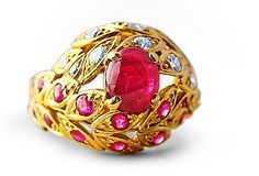 Bombe style... Ruby and Diamond Vintage ring  $2000  This is a beautifully proportioned Ruby and Diamond ring and for a large ring it looks fantastic on even a slender finger.    The centre Cabachon Ruby is 2.50 carats and there are 0.50 carats of small Rubies running up one side of the leaf motif and 0.30 carats of Diamonds up the other side.    It is 18 carat yellow gold and is signed KUT - which could be the famous London jeweller Kutchinsky of Knightsbridge.