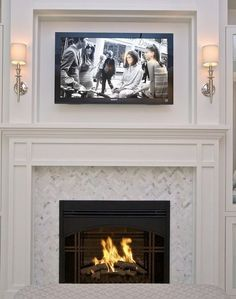 Beautiful fireplace mantel and surround with elegant sconces and mosaic tile