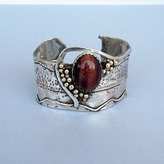 Cyndie Smith: Eye of the storm | Beautiful red tiger's eye cab set in fine silver on a forged, hammered and oxidized sterling silver cuff. Brass accent balls.