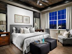 A rich wood plank ceiling accentuates this contemporary gray master bedroom. The bed features a padded gray headboard, and two square ottomans at the foot of the bed provide extra seating.