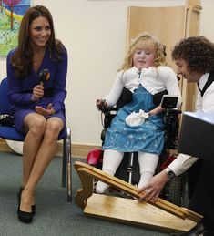 Catherine, Duchess of Cambridge joins in a music class alongside Bethany Woods in a music class during a visit to open The Treehouse Children's Hospice on March 19, 2012 in Ipswich, England.