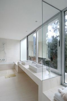 I love the way this vanity is divided by a glass panel and then their is a make-up area off the side.  Genius.