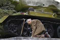Some pretty powerful photos - A Russian war veteran kneels beside the tank he spent the war in, now a monument.