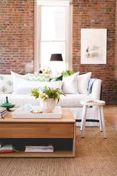 Exposed brick wall in living room with white couch and patterned pillows