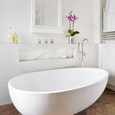 Modern white bathroom with spoon-shaped bath