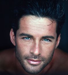 dark hair, well groomed beard, long eyelashes, a dusting of freckles and deep green oh so sexy eyes