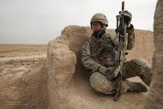 A soldier from the 1st The Queens Dragoon Guards (QDG - The Welsh Cavalry), sits on a rooftop suveying the area for signs of enemy movement. A Squadron from 1 QDG formed part of the Brigade Reconnaissance Force (BRF) with soldiers from 1 YORKS and carried out a partnered operation with the Afghanistan National Security Forces from 3/215 Brigade in an area that was previously an insurgent stronghold.