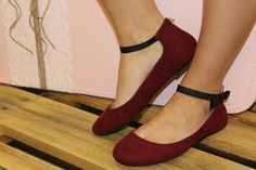 Turn heads with this Faux suede ballet style flat. Black side bow accents the ankle strap on this burgundy shoe.This shoe has a cushioned insole and heel goldto