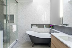 Modern bathroom featuring marble tile walls, inset mosaic tile shelves, shower and clawfoot tub. Munro Renovation by Wanda Ely Architect, Inc.