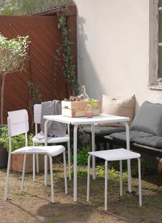 A sunny backyard with a white table, two chairs and a stool.