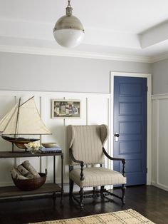 This fresh transitional foyer features light gray walls and a bold blue front door. Tall wainscoting adds a statement, while a neutral striped upholstered armchair provides a traditional touch. Sailboat decor gives the space a nautical vibe.