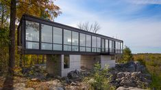This steel-and-glass box above an abandoned quarry in West Virginia is designed by Wiedemann Architects to provide live-work space for a Parisian sculptor.
