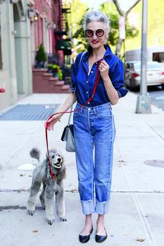 Mujer mayor usando un conjunto de mezclilla, tirantes rojos, tenis y sujetando a un perro con una correa