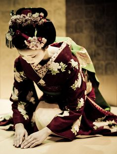 Geisha in kimono kneeling in respect.