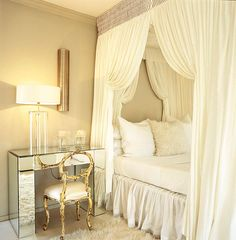 A dreamy bedroom dressed in ivory exudes 18th-century colonialist style with dramatic drapery and crystalline details. The frothy white mosquito netting can be tightly drawn at night for a cozy fortress; fluffy white pillows at the bed match the plush rug below.