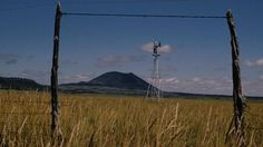 Capulin Volcano, in the distance, is framed by gate posts and a windmill from the plains. Capulin Volcano National Monument New Mexico