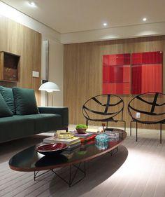 Painéis de madeira revestem as paredes deste apartamento e acolhem moveis de design e obras de arte contemporânea. Foto @pedroarielsantana