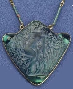 """eyesaremosaics:  """"Lalique 1913 signed 'Femme Dans Les Fleurs' Pendant: 2"""" high & wide triangle shaped w/additional rise on top, metal-backed glass, designed with a reclining nude female figure amid foliage, cabochons at each corner; baton link chain..."""