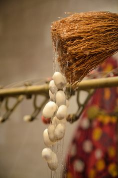 Silk worm cocoons about to be unspun.    History of Silk :  Since the 27 th century B.C., the Chinese have produced and used silk fabric. In fact, raising silk worms was one of the many chores of the farm women in China. From China, silk was exported via the Silk Route.    The Chinese never let out the secret of how the silk was produced. However, in later years, Christian monks smuggled the eggs out of the country; hence introducing silk manufacture in other nations as well.