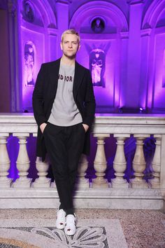 """Alessandro Borghi in a knit sweater with """"Blind for Love"""" embroidery, wool coat, black trousers and white leather Ace sneakers with star details."""